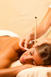 Woman with ear candles and gem massage